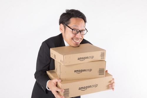 amazonの箱を抱えた男性